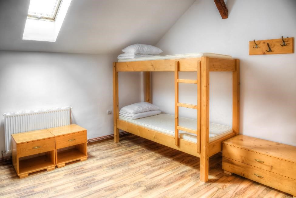 empty dorm room with a bunk bed, two bedside tables, and a small dresser