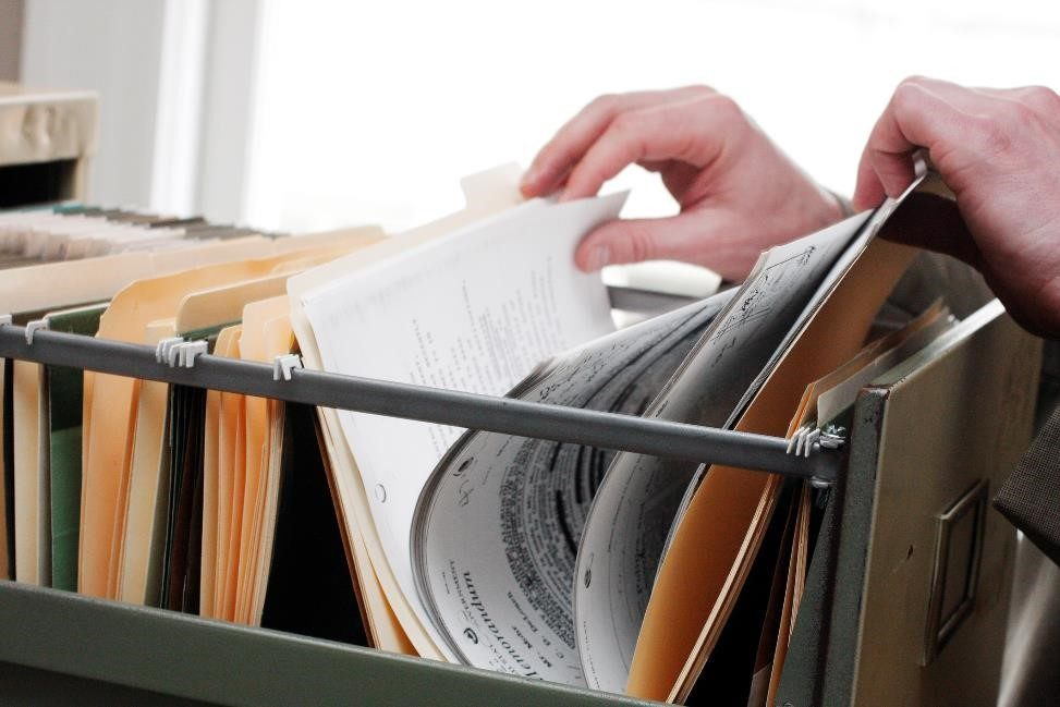 a person rifling through a drawer in a filing cabinet