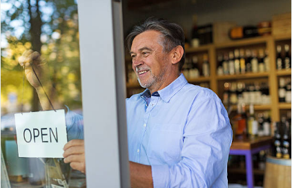 older man flipping sign in store window to 'open'