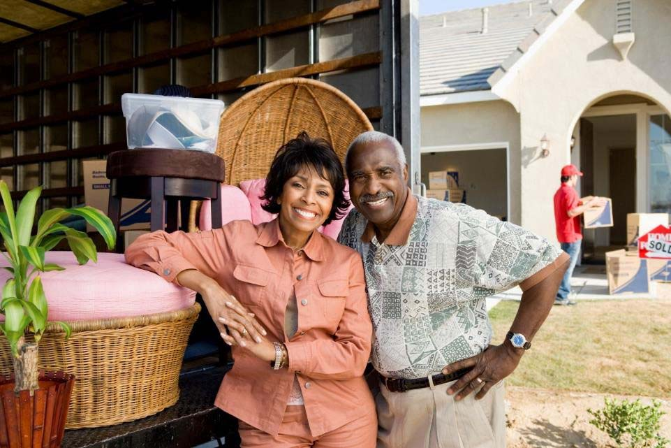 man and woman standing next to a moving truck full of furniture at their new home