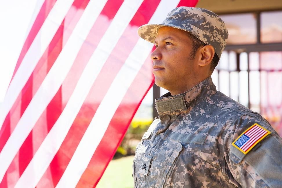 man dressed in military uniform standing before the U.S. flag