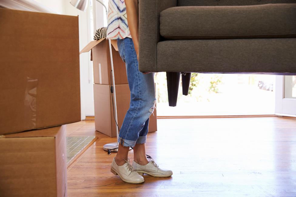 A woman carries one end of a couch