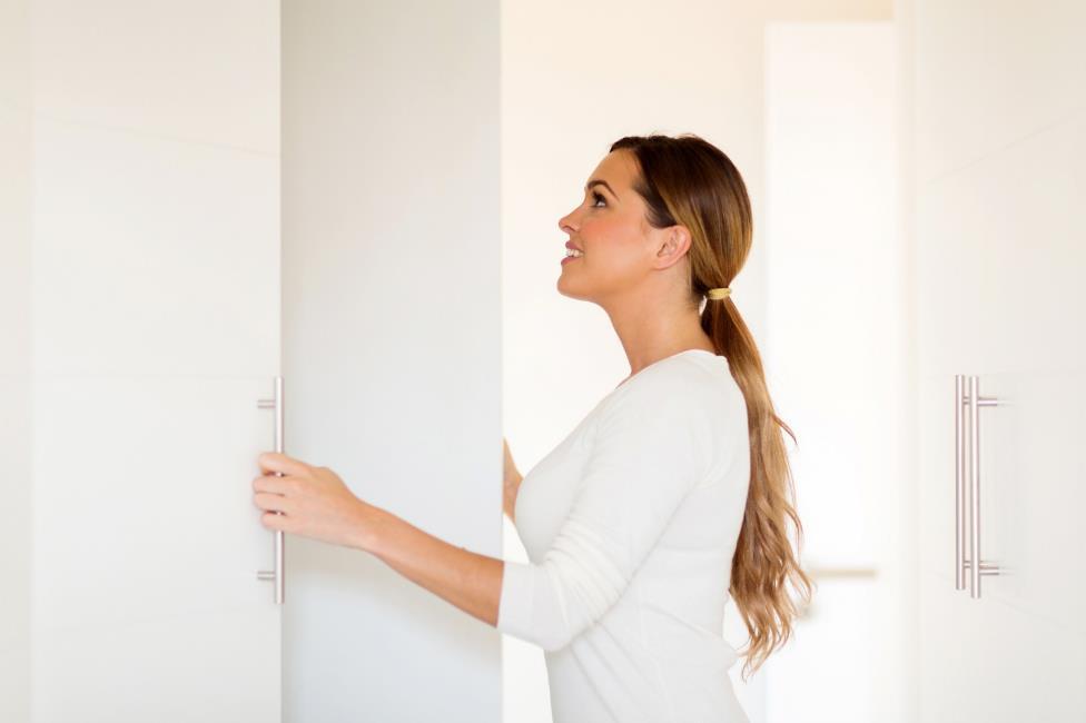 Woman opening white closet doors.