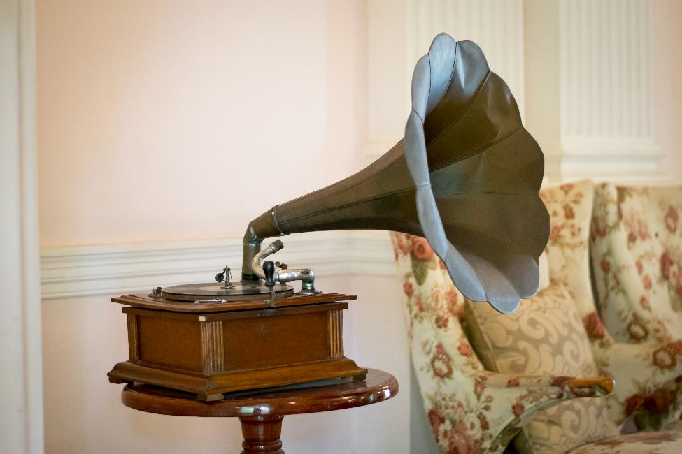 An antique record player with horn sitting on a side table.