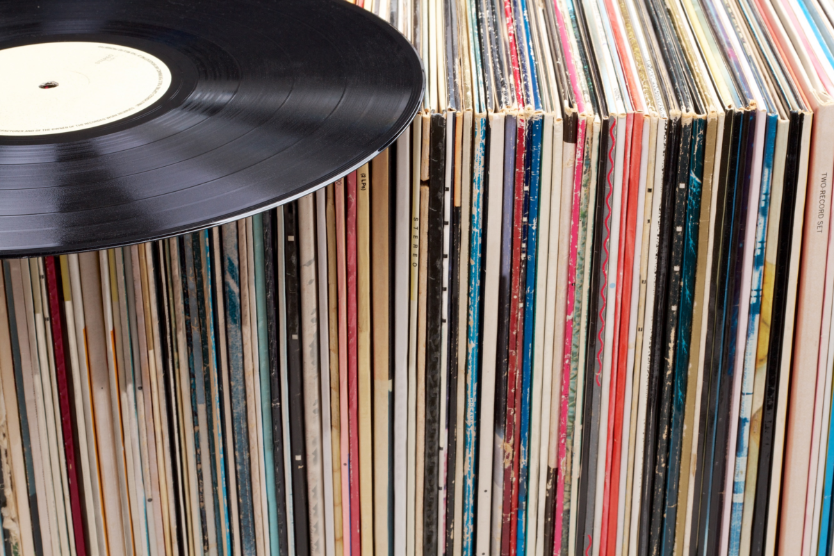 A record player disc laying on top of a shelf of record player albums.