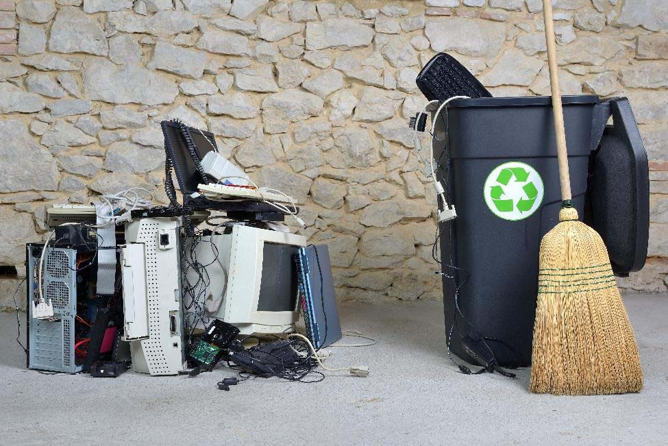 Old electronics sitting next to a recycling bin and broom.