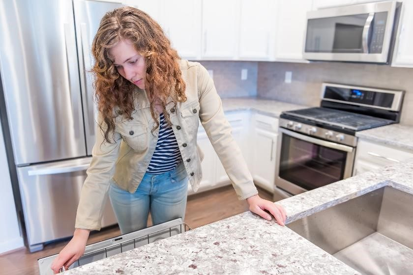 Woman examining granite counter top inside an apartment.