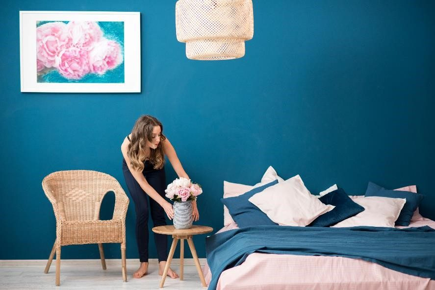 Woman decorating in blue bedroom.