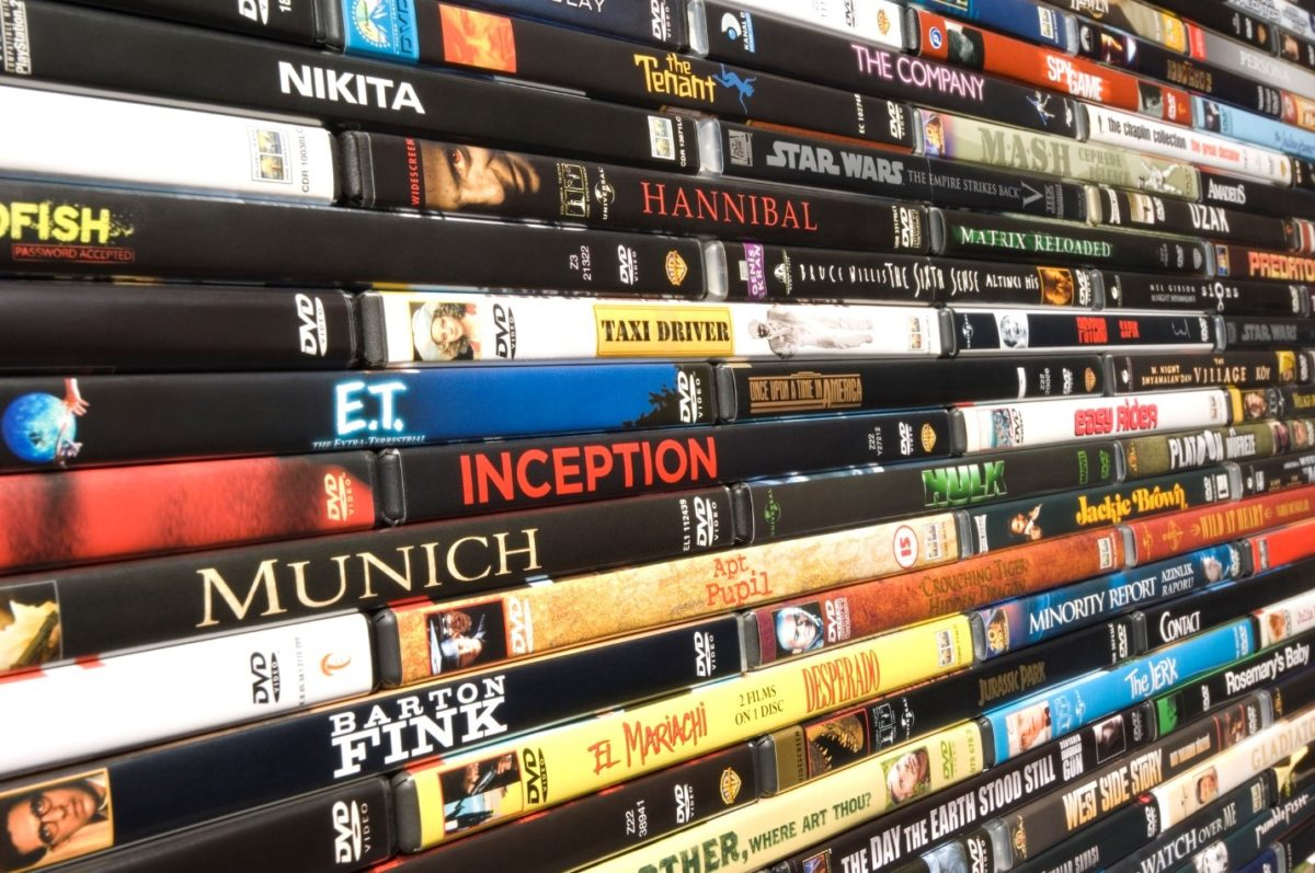 A large stack of DVDs on a storage shelf.