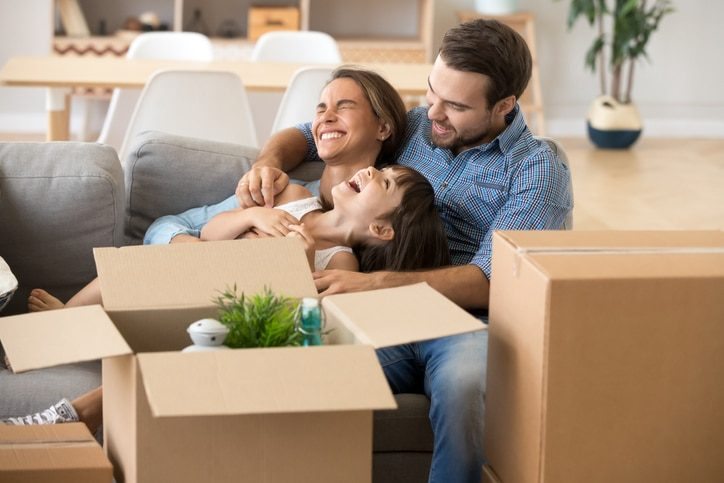 A smiling family sitting on their couch among moving boxes.